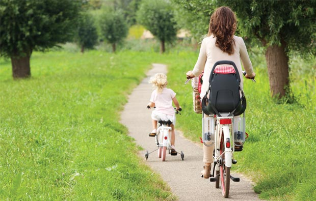 Mother and child cycle on a country path